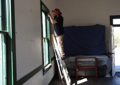 Jesse Haro working inside to remove a window