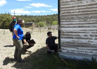 Mark Minor identifies a place on the siding where the original paint can be seen. Also pictured are Barbara Darden, Jon Sargent and Jesse Haro.
