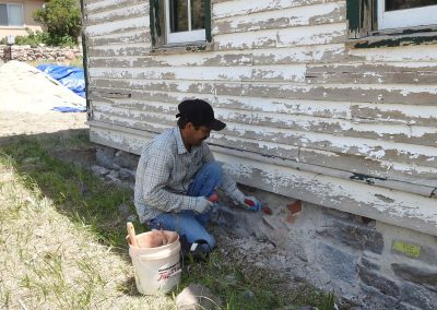 Thaddeus Hust is the sub-contractor for the foundation repair.  Pictured is Leo, his helper, preparing the foundation for new mortar.
